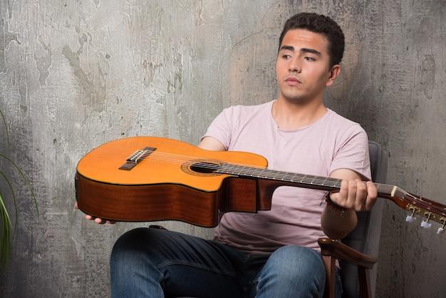 Молодой музыкант смотрит на гитару на мраморном фоне