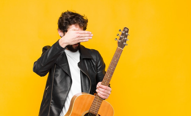 Young musician man covering face with both hands saying no! refusing pictures or forbidding photos with a guitar, rock and roll concept