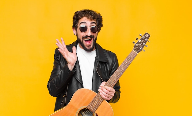 Young musician man feeling shocked and excited, laughing, amazed and happy because of an unexpected surprise with a guitar, rock and roll concept