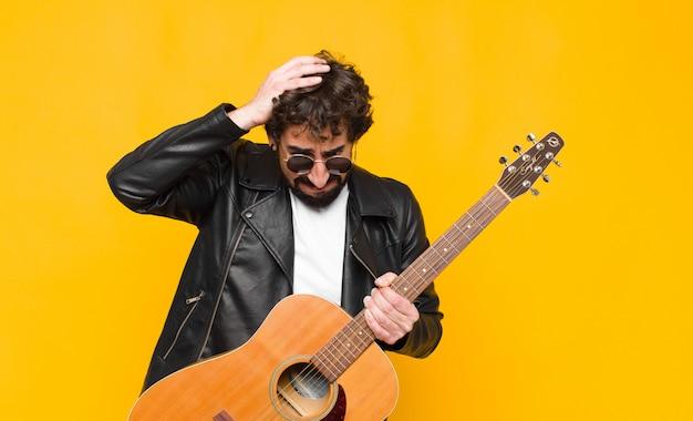 ストレスと欲求不満を感じて、頭に手を上げて、疲れて、不幸に感じて、片頭痛とギター、ロックンロールのコンセプトを持つ若いミュージシャン男