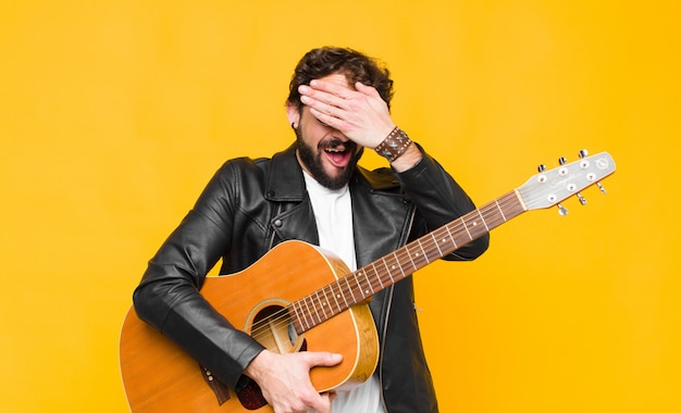 Young musician man smiling and feeling happy, covering eyes with both hands and waiting for unbelievable surprise with a guitar