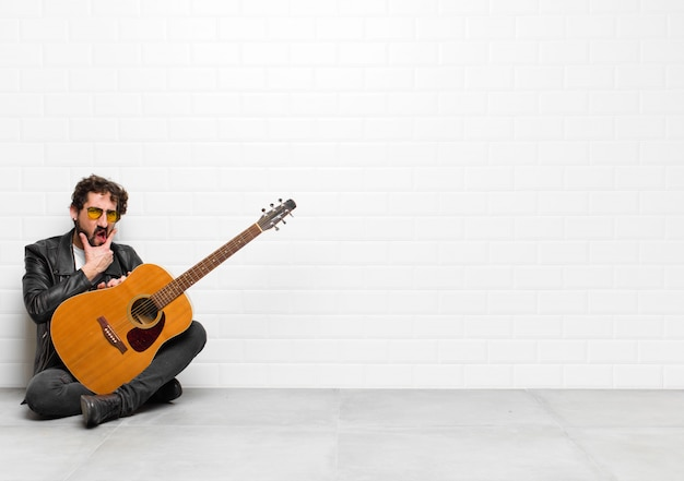 Young musician man with mouth and eyes wide open and hand on chin, feeling unpleasantly shocked, saying what or wow with a guitar, rock and roll concept