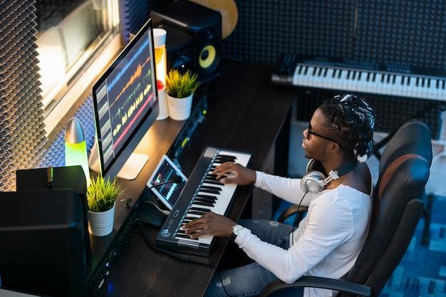 Молодой музыкант африканской национальности сидит в студии записи, создает новую музыку и микширует звуки на компьютере