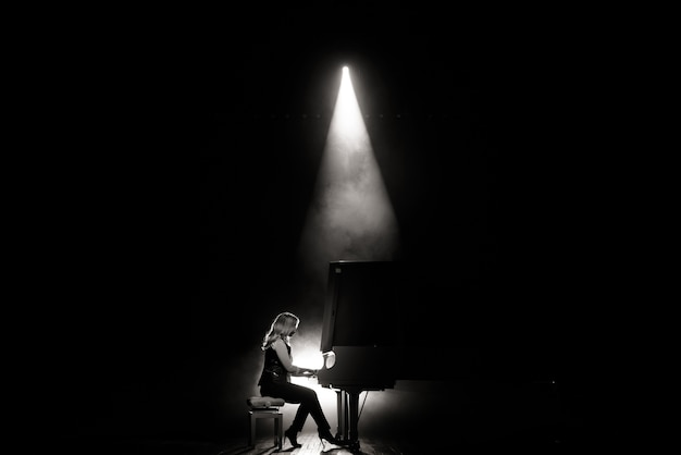 Young musician playing the grand piano on the stage in the beam of light