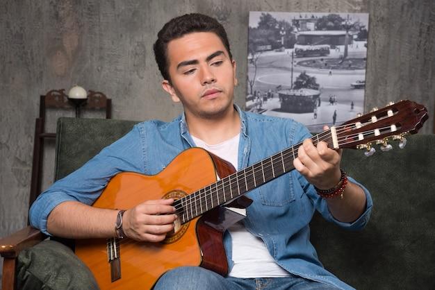 ギターを弾き、ソファに座っている若いミュージシャン。高品質の写真