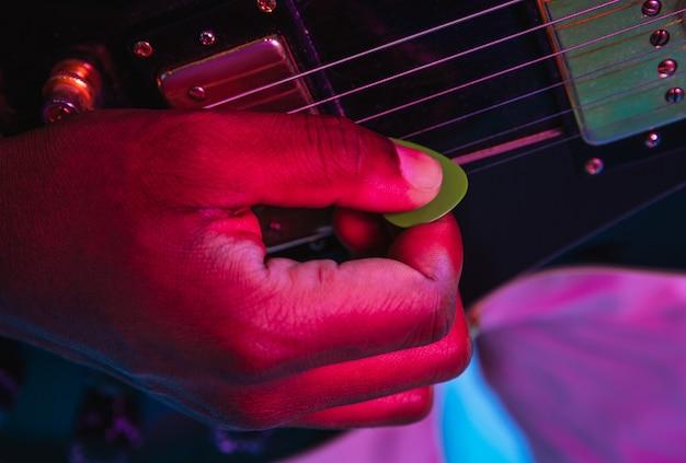 네온 불빛에 파란색 배경에 록 스타처럼 기타를 연주하는 젊은 음악가.