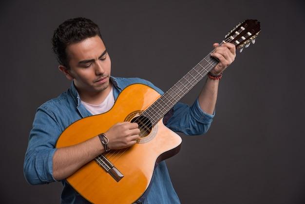 Молодой музыкант играет на гитаре на черном фоне