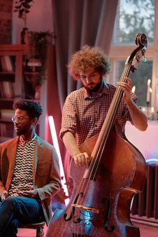 Молодой музыкант играет на скрипке во время выступления в клубе