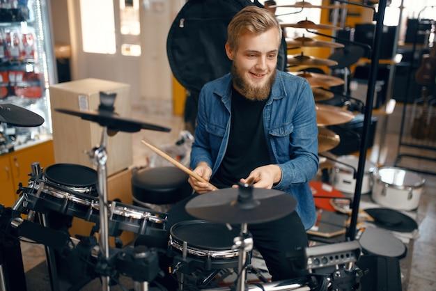 Молодой музыкант играет на барабанной установке в музыкальном магазине