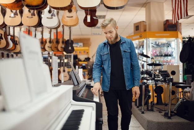 Молодой музыкант позирует за фортепиано в музыкальном магазине