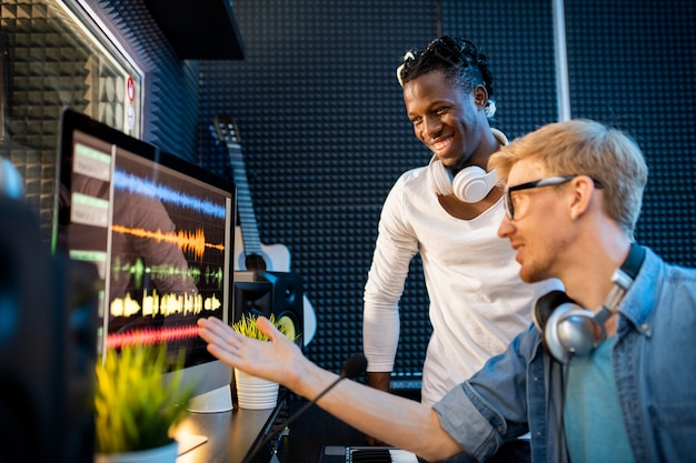 Young musician or producer showing african man group of sound waveforms on computer screen while working in team