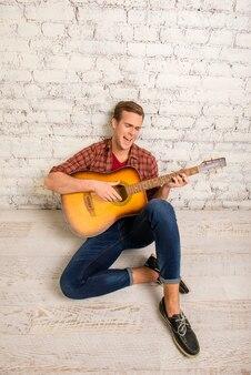 ギターと歌を床に座っている若いミュージシャン