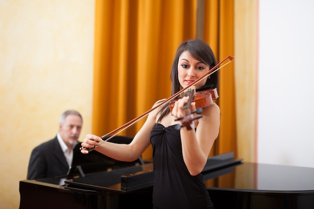Young musician woman playing her violin