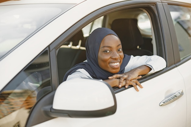 Young muslim african woman pose with hands on car window line. waiting for someone, looking at camera. white car.