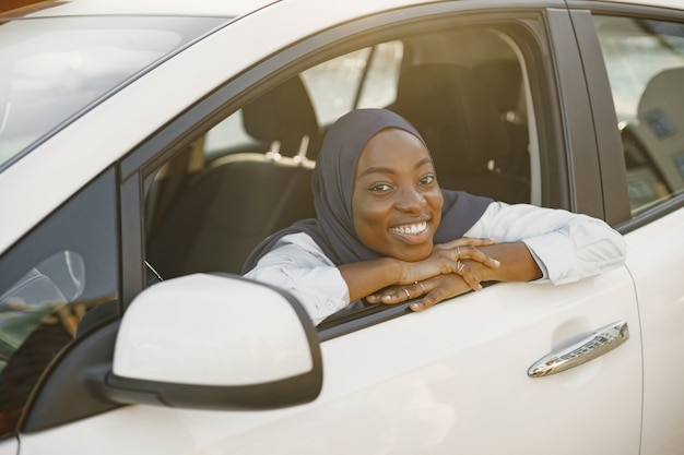Young muslim african woman pose with hands on car window line.