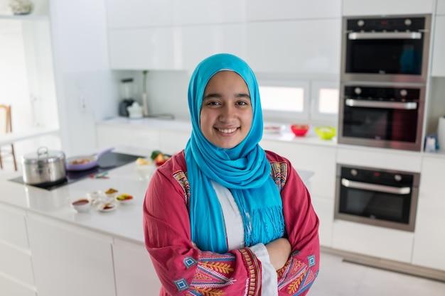 부엌에서 젊은 무슬림 아랍어 여자