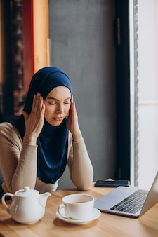 Young muslim business woman having head ache and working online on a computer