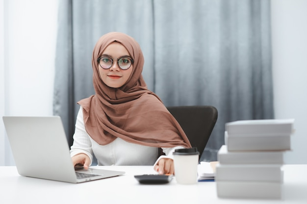 Young muslim business woman wearing brown hijab working with laptop computer in her house.