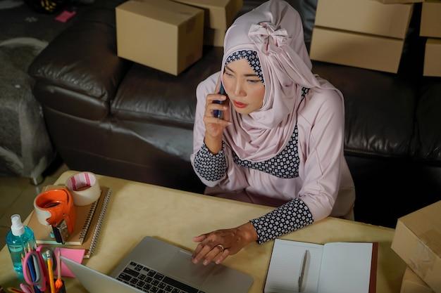アジアの若いイスラム教徒の実業家は、在庫商品の注文をチェックし、ホームオフィスのタブレットコンピューターに保存します。中小企業の所有者がオンラインマーケットを送信するcovid-19の発生時に、コンセプト
