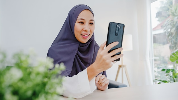Young muslim businesswoman using smart phone talk to friend by videochat brainstorm online meeting while remotely work from home at living room.