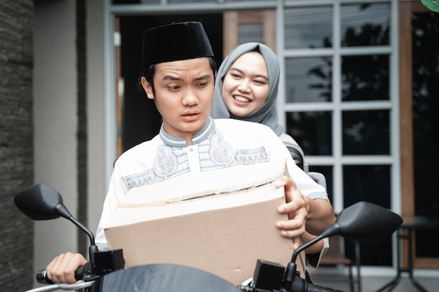 Young muslim couple by motorcycle going home carrying lots goods