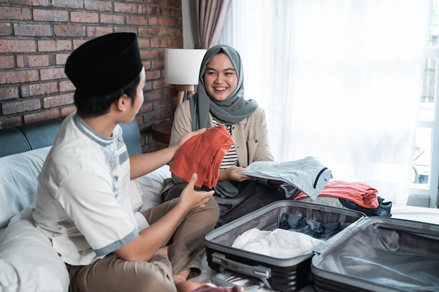 Young muslim couple prepare luggage together