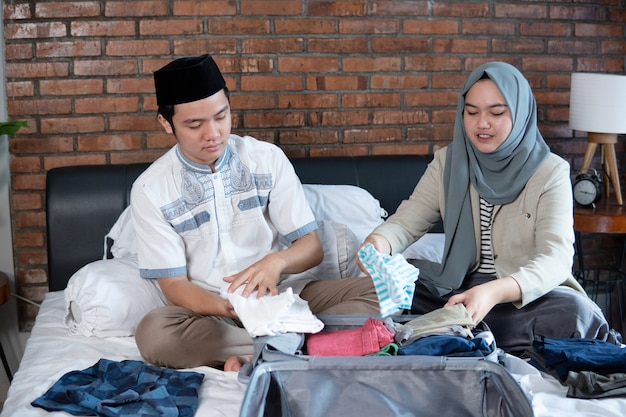 Young muslim couple prepare luggage