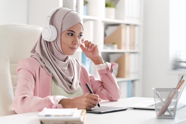 机に座って、ウェブデザインを作成しながらデジタルスケッチに取り組んでいるピンクのベールの若いイスラム教徒のデザイナー