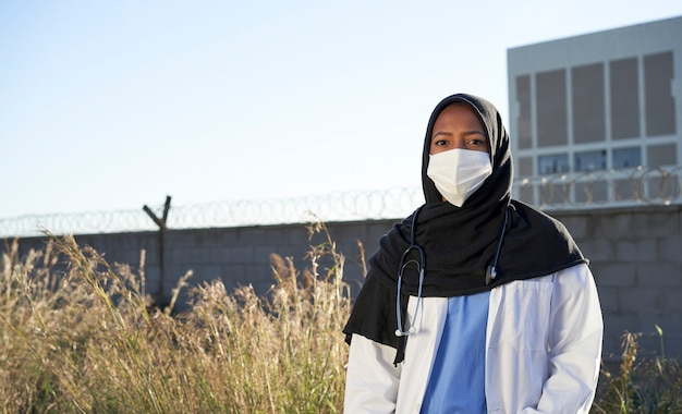 A young muslim doctor with a headscarf outdoors. islamic doctor with hijab is standing outside in a poor area facing the camera. volunteer doctors.