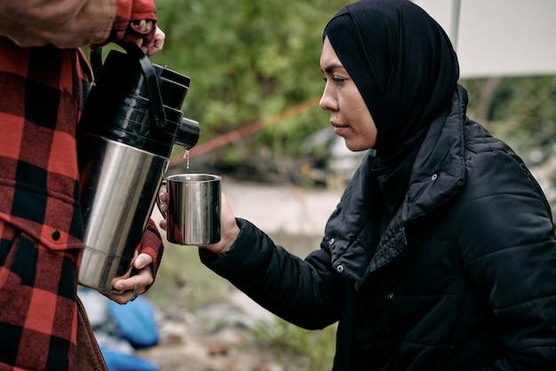 ボランティアがお湯を注いでいる間マグカップを保持している黒い服を着た若いイスラム教徒の女性