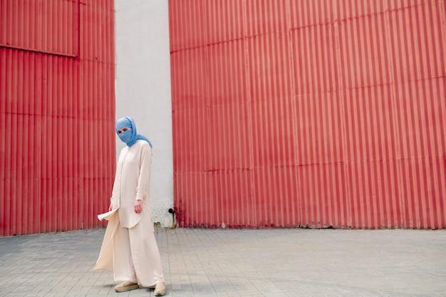 青いヒジャーブと壁の外壁に立っているカジュアルウェアの若いイスラム教徒の女性