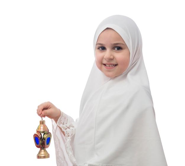 Молодая мусульманская девушка в хиджабе с фонарем рамадан