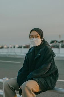 검은 머리 스카프와 얼굴 마스크를 쓴 젊은 이슬람 소녀