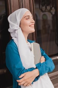 若いイスラム教徒の少女は日記の本イスラム学生と知識の概念とヒジャーブを身に着けています