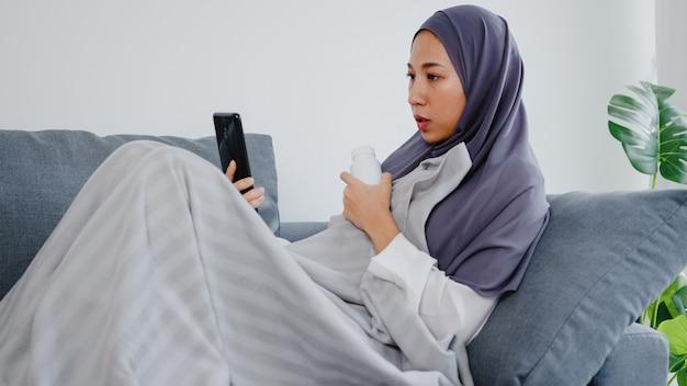 La giovane donna musulmana indossa l'hijab usando la videochiamata telefonica parlando con la consultazione del medico o la consultazione online sul divano nel soggiorno di casa.