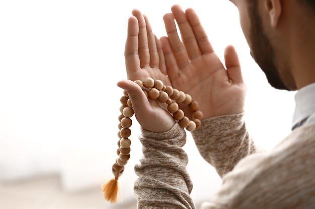 Молодой мусульманин молится в помещении