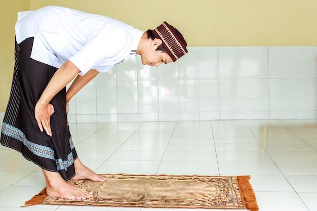 祈祷マットにルクジェスチャーで若いイスラム教徒の男性のサラッ