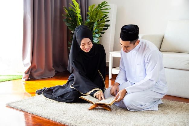 Young muslim man teaching pretty woman read koran