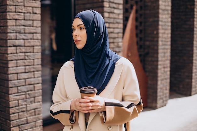 Young muslim woman drinking coffee