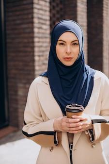 Молодая мусульманская женщина пьет кофе
