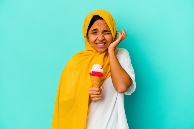 手で耳を覆う青い背景で隔離のアイスクリームを食べる若いイスラム教徒の女性。