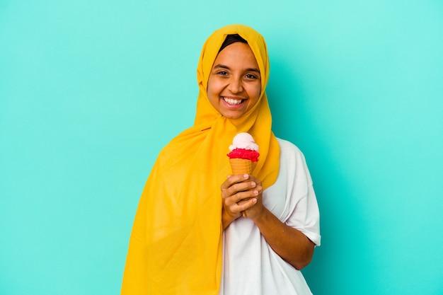 青い背景に分離されたアイスクリームを食べる若いイスラム教徒の女性は幸せ、笑顔、陽気な。
