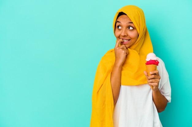 Молодая мусульманская женщина ест мороженое, изолированное на синем фоне, расслабленно думая о чем-то, глядя на копию пространства.
