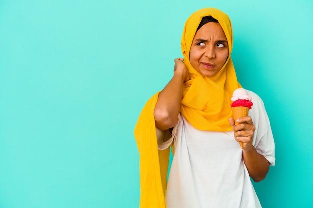 Молодая мусульманская женщина ест мороженое, изолированное на синем фоне, касаясь затылка, думая и делая выбор.