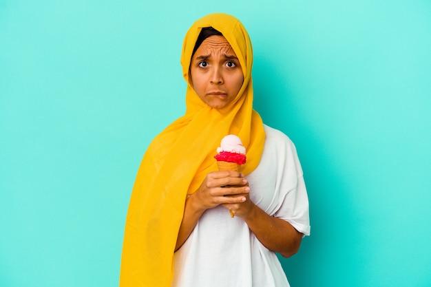 파란색 벽에 고립 된 아이스크림을 먹는 젊은 무슬림 여성은 혼란스럽고 의심스럽고 확신이 없습니다.