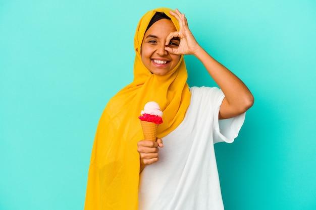 파란색 벽에 고립 된 아이스크림을 먹는 젊은 무슬림 여성이 눈에 확인 제스처를 유지 흥분.