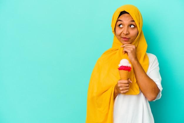 의심스럽고 회의적인 표정으로 옆으로 보이는 파란색 벽에 고립 된 아이스크림을 먹는 젊은 무슬림 여성.