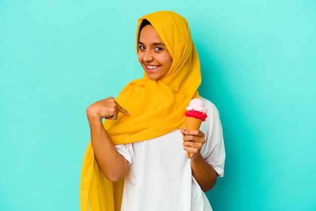 誇りと自信を持って、シャツのコピースペースを手で指している青い壁の人に分離されたアイスクリームを食べる若いイスラム教徒の女性
