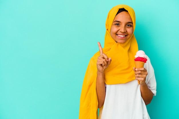 손가락으로 번호 하나를 보여주는 파란색 벽에 고립 된 아이스크림을 먹는 젊은 무슬림 여성.