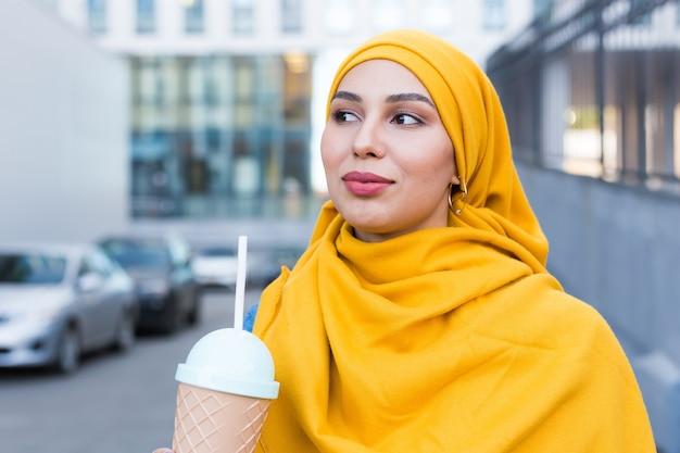 Молодая мусульманская женщина, наслаждаясь коктейлем на открытом воздухе